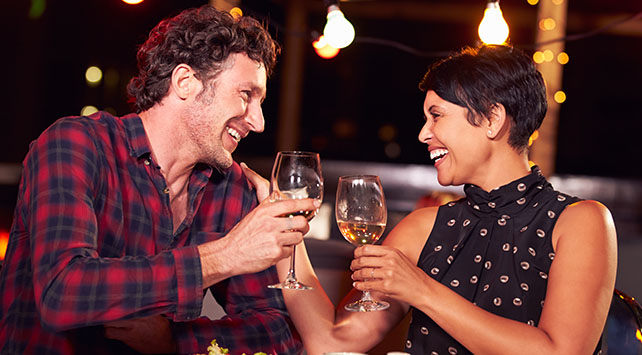 Couple enjoying their $25 dining credit - cheers with wine glasses
